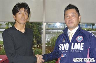吉野理事長(右)と握手を交わす有馬監督