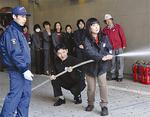 散水栓ホースの取扱いを学ぶ能楽堂の職員
