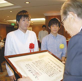 梅田会長から表彰状が贈られる落合さん(左)