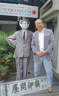 店の前で初代社長のパネルと鈴木社長