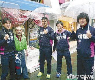 雨の中、商店を回る選手たち