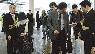 「飲酒ルールの徹底を」と通行人に呼びかける参加者(右)