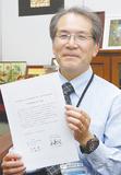 合意書(写し)を手にする宮崎校長
