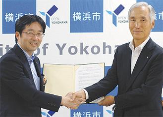 協定締結式で握手を交わす大前理事長(右)と鯉渕局長