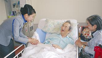 入院患者にしおりを贈る山口さん(左)