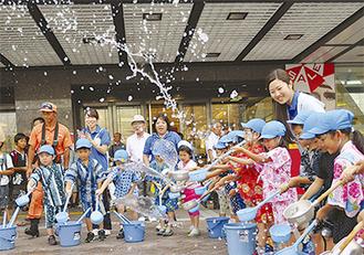 打ち水を楽しむ園児たち