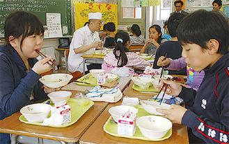 5年生と和献立てを味わう武本さん(中央)