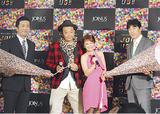 オープニングイベントに登場したTKO木下さんと鈴木奈々さん。お祝いの巨大クラッカーを片手に佐藤充取締役(右)と西口文雄所長
