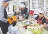 児童に料理法を指導するぐるめ・にしのメンバー
