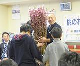 桃の花を寄贈する坪倉会長