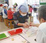 鈴木さんから色付けを教わる児童