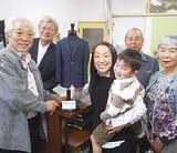 田中さん(中央)へ製作者の渡辺さん(左)から思い出の一着が手渡された