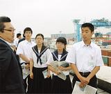 児島所長(左)の説明を聞く生徒たち=9日