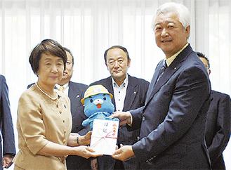 目録を手渡す土志田会長(写真右)