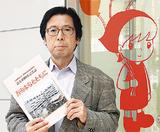 記念誌を手にする徳田理事長