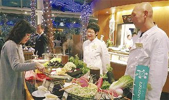 ブッフェ台で野菜の説明をする生産者