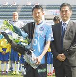 YSCCの吉野次郎理事長(右)から記念の花束を受け取る吉田選手