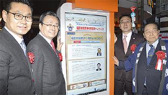 デジタル掲示板を囲む平山会長(右)ら
