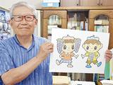 「ふじこちゃん」と「ふじおくん」のイラストを手に笑顔の鈴木さん