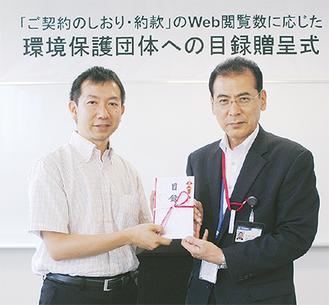 目録を手渡すかんぽ生命の志子田支店長(右)と、よこはま里山研究所の松村理事長