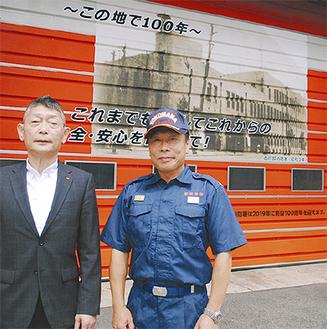 塗り替えたシャッターの前に立つ、火災予防協会の緑川会長(左)と西消防署の中嶋署長