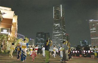 みなとみらいの夜景を見ながら輪になって踊る住民たち。すいか割りや金魚すくいなども行われ、約150人が楽しんだ