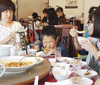 中華料理を頬張る子どもたち