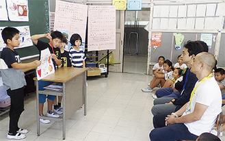 高橋社長(=右手前から2番目)ら社員を前に、真剣な表情でメニューのプレゼンをする児童たち=10月12日
