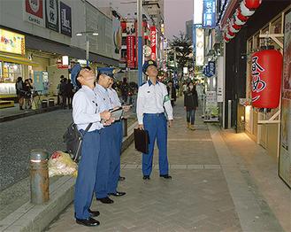 商業ビルを外部からチェックする消防局職員=横浜駅西口