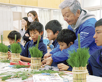 とび職人の小島正男さんから門松づくりを教わる生徒たち=11日、横浜吉田中学校