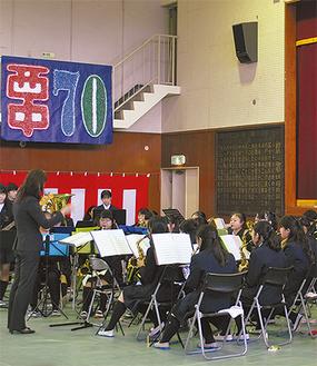 生徒の記念制作を背に吹奏楽部が演奏