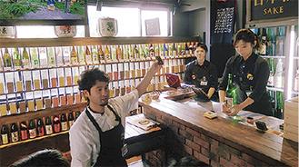 立ち飲みエリアで説明する田所社長。注文時はギャラリーのように酒瓶が並ぶ棚から値段ごとに色分けされた枡を選ぶ