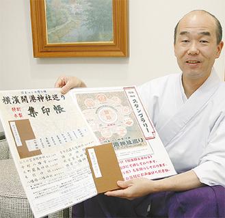 神社巡りの資料を手にする本牧神社の當麻宮司