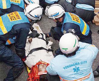 要救助者役の人形を搬送する西消防団員と戸部警察署員(西消防署提供)