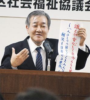 横浜市社協設立時のスローガンを手にあいさつする天笠会長