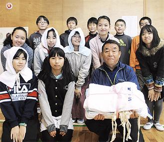 代表して防災頭巾を受け取った、第4地区自治会連合会の林和明会長(前列右端)と一本松小6年1組の児童たち