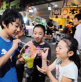 シロップ「全部がけ」の大盛りかき氷をみんなで食べる子どもたち
