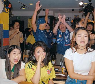 香川選手のPKが決まり呆然とするコロンビアサポーターの後ろでは歓喜の笑顔が