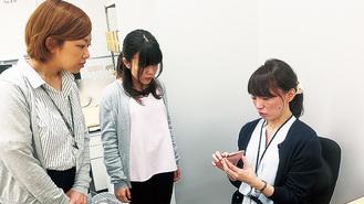 女性社員(右)から業務内容について説明を受ける、研修参加者ら