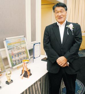 一本松SCの河合代表総監督。会場には歴代の表彰杯やユニフォームも飾られた