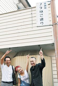 新たに設置された看板。猫のイラストが隠れているロゴは、女子美大の学生がデザイン(右から佐藤会長、鈴木さん、吉田理事長)