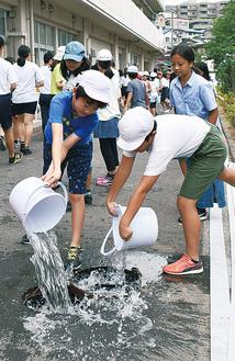 災害用トイレに使用する貯水のために児童がバケツリレーも