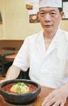 「スーラータン炒飯」を紹介する金葉の林店長