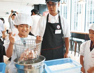 本社にある「テストキッチン」を利用して、鶏肉を「つなぎ」につける作業を行う子どもたち。揚げる直前までの工程を体感した