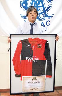 贈呈されたシェフィールドFCのユニフォームを持つ細貝理事長