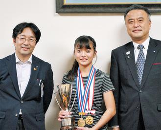 メダルとトロフィーを持つ中里さん(中央)と小林一美副市長(右)、鯉渕信也教育長
