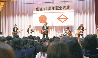 総立ちの生徒を前に演奏する岸さん(中央)