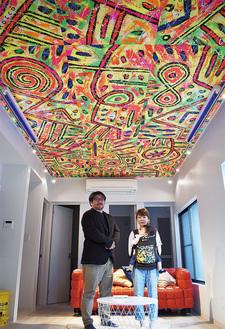 ロコサトシさんの作品が天井を飾る「HACO」1階の共有スペース。両商店街の佐藤会長(左)と飯田会長