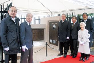 顕彰碑完成を祝う渡邊家の子孫や中大関係者たち。バス通りから見えるよう、碑はL字で製作された