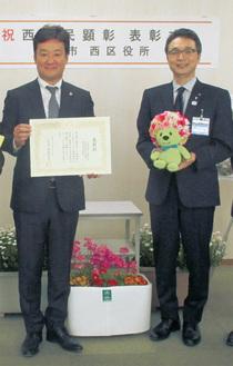 表彰状を受け取る迫田支部長(左)